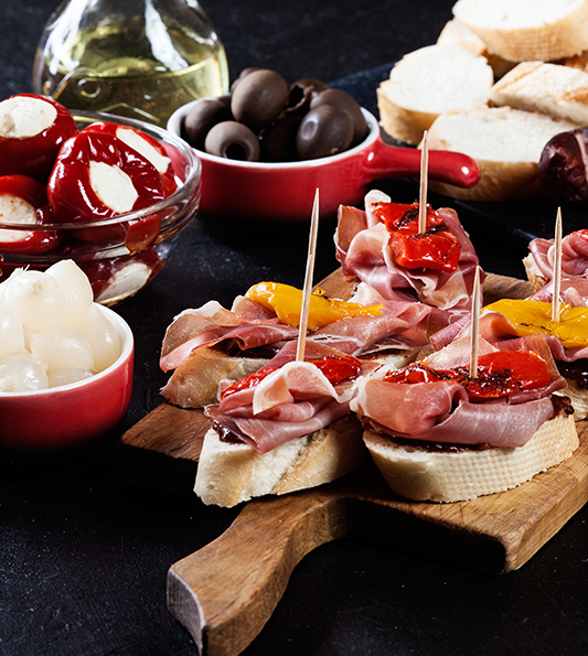 Spanish tapas with slices jamon serrano and grilled pepper. Also olives, salami, pickled onions, and peppers stuffed with cheese. Spanish cuisine